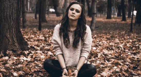 femme assise au milieu des feuilles mortes